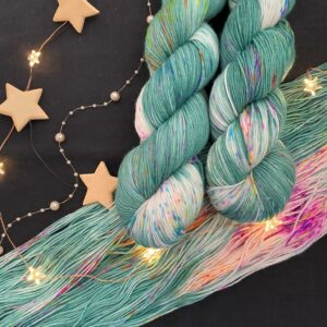 two twisted skeins of yarn are shown over an open skein on a black background. The yarn is a pine green with large white areas that are covered in neon pink, orange and yellow speckles. Knit and crochet swatches are in the centre of the image, with springs of pine tree on the upper right. A string of colourful fairy lights flows over the image.