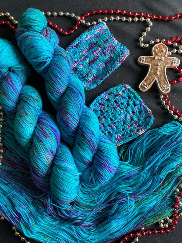 two twisted skeins of rich jade yarn speckled with pinks and purples lay on top of an open skein. To the left are small knit and crochet swatches, a gingerbread man ornament and some red and silver decorative strings of beads. Everything is on a black background.