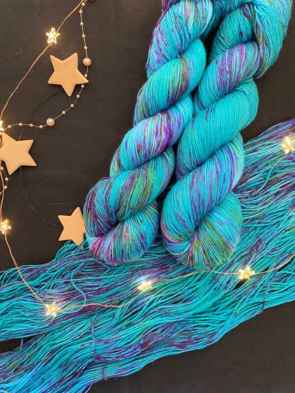 rich jade green blue skeins covered with pink and purple jewel toned speckles. Two skeins lay twisted onto an open skein with wooden stars and fairy lights surrounding them, all on a black background