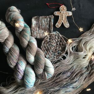 two skeins of soft brown yarn, with flashes of white and speckles of jade and purple lay to the left of a black background. along the bottom is an opened skein of the same colour way, with knit and crochet swatches in the centre. on the right is a gingerbread person ornament and fairy lights are scattered throughout the image.
