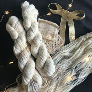 two twisted, neutral coloured & lightly speckled skeins lay on a open skein. There are swatches to the right, a large gold bow and twinkly fairy lights, all on a black background. The yarn is creamy, with a subtle hint of taupe and delicately speckled with pinks, blues and coral.