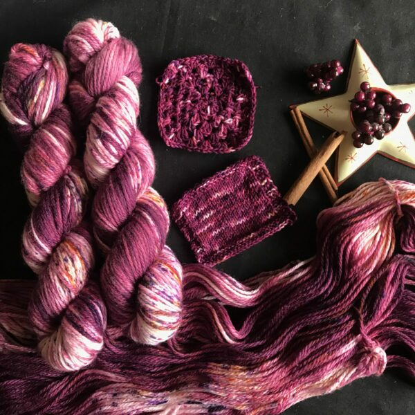 two deep red wine coloured skiens, speckled with purples and reds are laid over an untwisted skein on a black background. Knit and crochet swatches are shown in the centre on the image with a star shaped ctralight holder filled with fake pink berries and cinnamon sticks to the right of the image