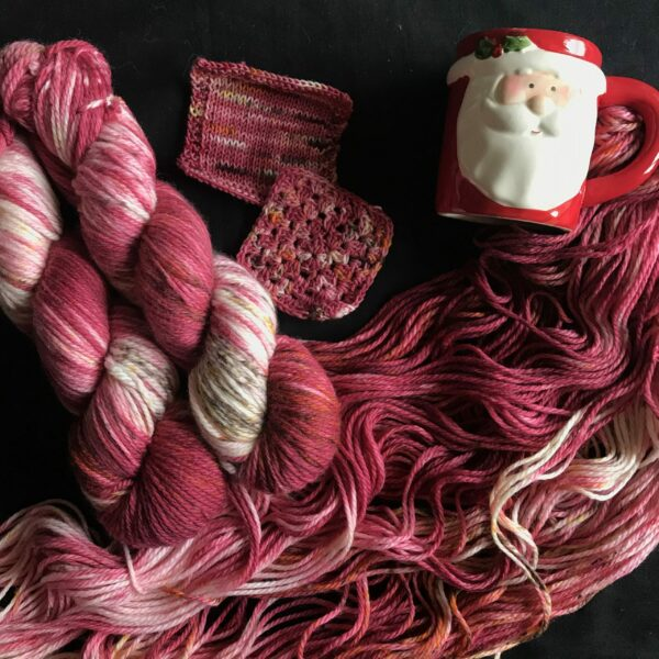 two bright red skiens are shown twisted next to an opened skein. The red yarn has white flashes and is speckled with browns and yellows. Knit and crochet swatches are shown on the black background next too a red novelty Santa mug.