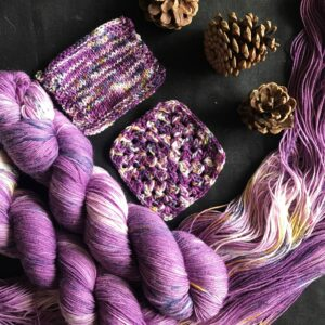 two plummy purple skeins lay twisted next to an open skein and knit/crochet swatches. The plummy yarn has white flashes and speckles of navy and gold. Pine cones are scattered onto the black background