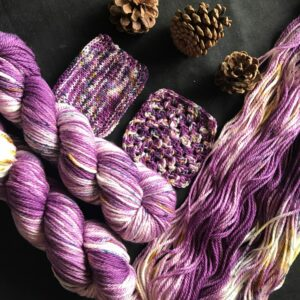 two plummy purple aran skeins lay twisted next to an open skein and knit/crochet swatches. The plummy yarn has white flashes and speckles of navy and gold. Pine cones are scattered onto the black background