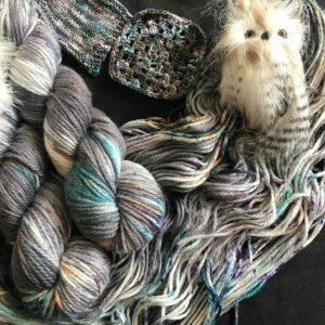 two skeins of plump yarn are shown over an open skein. The yarn is dark grey and white with flashes of purple, gold and jade speckles. Knit and crochet swatches are shown and a fluffy owl ornament is nestled in the open skein