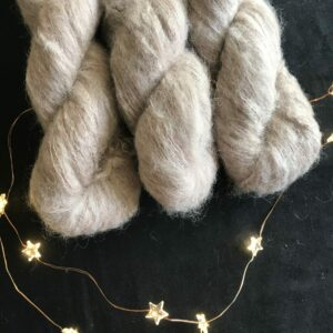 a black background is decorated with star shaped fairy lights. Coming from the top edge are three twisted skeins oil fluffy lace weight yarn. The yarn is a soft, oyster shade, with a hint of very light brown to it. Its a lovely neutral shade.