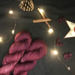 two dark, wine red twisted skeins are on a diagonal from the bottom left corner. They are placed on a black background lit with fairy lights and decorated with pine cones, cinnamon sticks, fake berries and a the edge of star shaped tea light holder