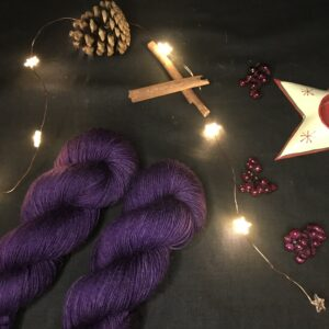 two deep, rich, dark purple twisted skeins on a diagonal from the bottom left corner. They are placed on a black background lit with fairy lights and decorated with pine cones, cinnamon sticks, fake berries and a the edge of star shaped tea light holder