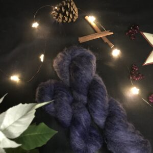 two twisted skeins of fluffy, very dark navy blue skeins are placed on a diagonal from the bottom right corner. They are on a black background lit with fairy lights and decorated with pine cones, cinnamon sticks, fake berries and a the edge of star shaped tea light holder can be seen, as well as leaves of a white poinsettia.