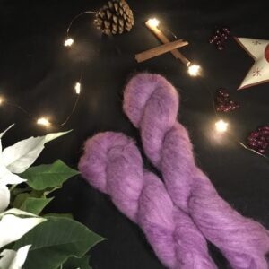 two twisted skeins of fluffy, pinkish plummy skeins are placed on a diagonal from the bottom right corner. They are on a black background lit with fairy lights and decorated with pine cones, cinnamon sticks, fake berries and a the edge of star shaped tea light holder can be seen, as well as leaves of a white poinsettia.