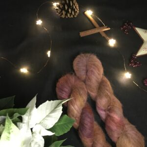 two twisted skeins of fluffy brownish/reddish/orangey tones are placed on a diagonal from the bottom right corner. They are on a black background lit with fairy lights and decorated with pine cones, cinnamon sticks, fake berries and a the edge of star shaped tea light holder can be seen, as well as leaves of a white poinsettia.