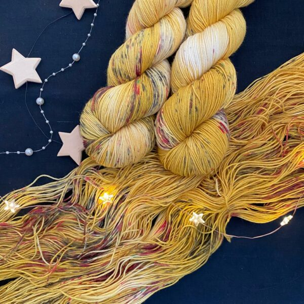 mustard coloured yarn, with areas undyed, speckled with black and pinky red. stars and fairy lights are scattered over the yarn