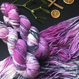 dark raspberry purple yarn with white flashes and speckled with black and purple. Two twisted skeins and laid flat on a black background decorated with mistletoe, dried orange slices and cinnamon sticks