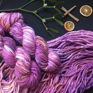 two twisted skeins are laid over a flat skein. All is shown on a black background decorated with cinnamon sticks, mistletoe and dried orange slices. The skeins are reddish-purple with lots of purple and orange speckles