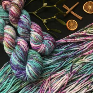 two twisted skeins are places over a flat skein. the yarn is dyed jade green with heavy speckles of pink, green and purple. All is shown on a black background decorated with cinnamon sticks, mistletoe and dried orange slices