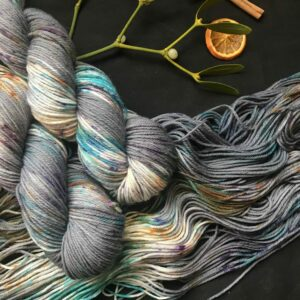 two dark grey skeins with flashes of white are twisted and laid over a flat skein. all skeins are speckled with greens, purples and oranges. they are on a black background decorated with mistletoe, dried orange slices and cinnamon sticks