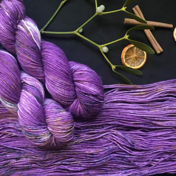 two twisted plummy purple skeins lay over an flat skein. they are speckled with blues and purples on a black background decorated with mistletoe, dried orange slices and cinnamon sticks