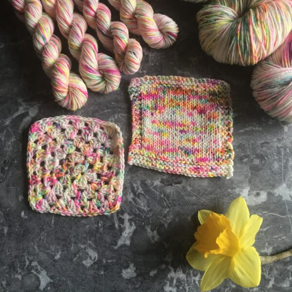 on a grey marble background are two knit and crochet swatches, 4 minis skiens at the top left and two full skeins peeking into the top right. a daffodil is at the bottom right. The yarn is a natural white base , covered in neon speckles - pink, orange, yellow, green. Every stitch is a different colour.