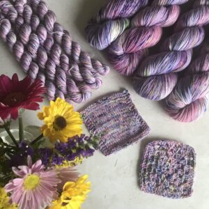 a posy of bright yellow and pink flowers is on the bottom left corner of an off white, plaster background. Knit and crochet swatches are in the centre with full skiens to the top right and minis to the top left. The yarn is a mix of soft pinks and purples, with flashes of white and lots of pink, blue, green and yellow speckles.