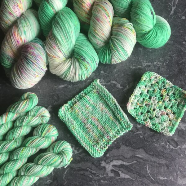 on a grey marble background are 4 full skeins at the top, 4 minis to the bottom left as well as knit & crochet swatches in the middle. The yarn is a bright minty green with white flashes and lots of neon pink and orange speckles.