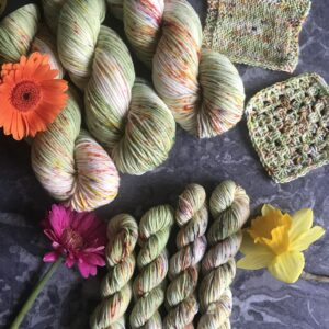 on a grey marble background are three full size skeins at the top left corner, 4 mini skeins coming from the bottom edge and knit & crochet swatches on the right. The yarn is a soft pistachio green with white flashes and speckles in coral, pink and yellow. A daffodil is at the bottom right, a pink germini at the bottom left and orange germini at the top left