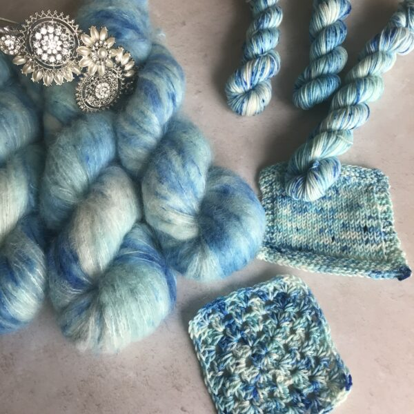 on an off white textured plaster background are three fluffy skiens with a diamond and pearl tiara on top, three mini skiens as well as knit and crochet swatches. the yarn is mix of soft blues and white with darker blue speckles all over the yarn.