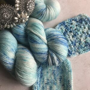 on an off white, plaster background are the rounded ends of three skeins of sparkle yarn, with a diamond and pearl tiara resting on top. also shown are knit and crochet swatches. The yarn is a soft blue and white with darker blue areas and a mix of blue speckles over the top.