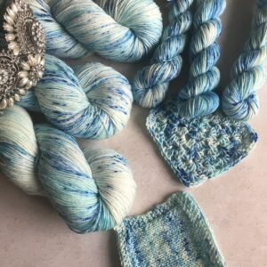 the rounded ends of three twisted skeins are placed at the top left corner of an off white plaster background. The edges of a diamond and pearl tiara can be seen on top of them. Also shown are mini skeins, knit and crochet swatches. The yarn is a mix of soft blues and whites with lots of darker blue speckles all over