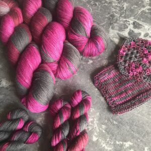 on a grey marble background are three full sized skiens at the top left and 4 mini skeins in the bottom left and centre. knit and crochet swatches are to the centre right. the yarn is a regular repeating variegated colour way shifting from charcoal grey into deep red and raspberry pink.