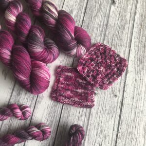 on a rustic, white wooden background are three full and three mini skeins as well as knit and crochet swatches. The yarn is deep raspberry pinks with a hint of purple and white, with lots of pink and black speckles all over.