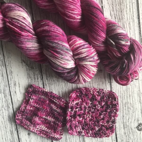 on a rustic, white wooden background are two full skeins as well as knit and crochet swatches. The yarn is deep raspberry pinks with a hint of purple and white, with lots of pink and black speckles all over.