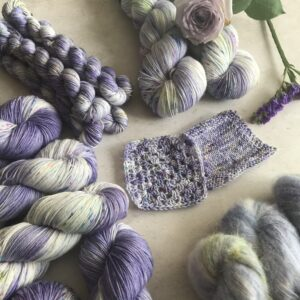 in the centre of an off white, plaster background are knit and crochet swatches, surrounded by clusters of skeins in varying weights, as well as a soft lilac rose and deeper purple flowers. The yarn is a soft lavender and white mix, with tonal areas and speckles in pink, blue and green.