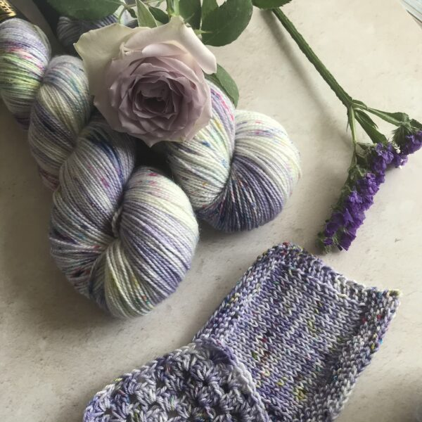 on an off white, plaster background are two twisted skeins of sparkly yarn. They are dyed a soft lavender with flashes of white and a mix of green, blue and pink speckles. A soft lilac rose is on top of the skeins with a small spring of dark purple flowers to the right. At the bottom of the image are knit and crochet swatches, which are partly showing.