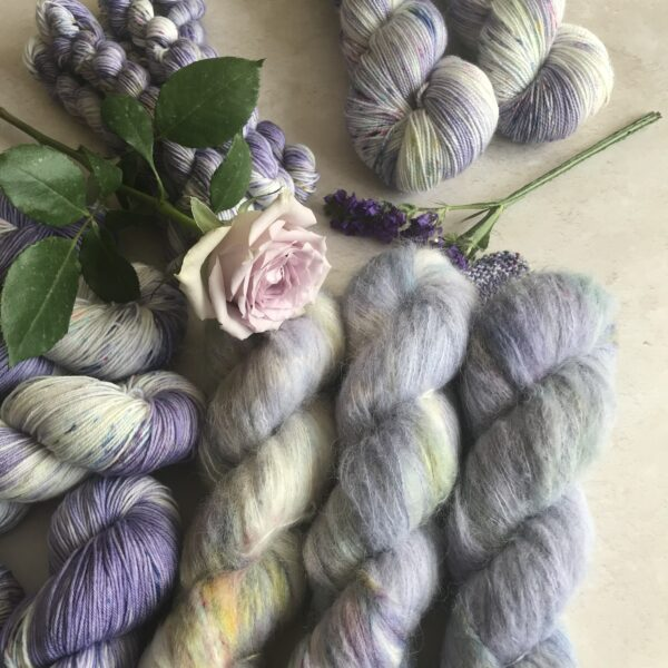 on an off white plastered background are several skeins of soft lilac coloured yarn with pink, lavender and green speckles, with white flashes in the yarn. The focus is on three fluffy skeins with mini skeins and non fluffy skeins around the image. A soft pinkish lilac rose is in the centre of the picture with some smaller purple flowers also.