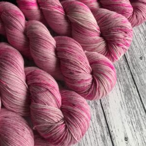 5 twisted skiens of soft rose pink yarn with neon pink speckles, placed at a diagonal on a white wooden background