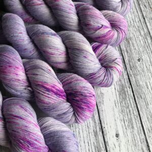 5 twisted skeins of lavender coloured yarn with neon purple and lilac speckles placed at a diagonal on a white wooden background