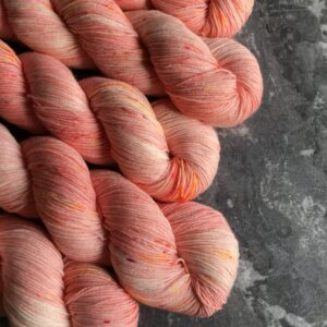 5 twisted skeins of coral coloured yarn with coral and orange speckles, placed at a diagonal on a grey marble background