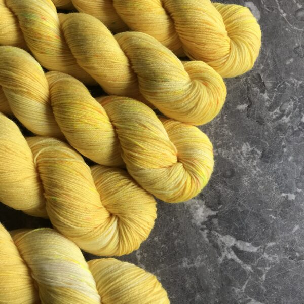 5 twisted skeins of daffodil yellow yarn with neon yellow and bright yellow speckles, placed at a diagonal on a grey marble background