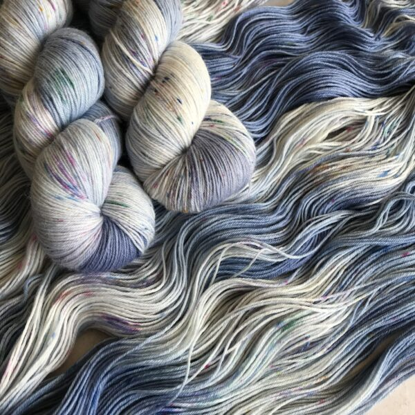 two twisted skeins lay on top of two opened skeins that are all dyed a delicate blue with a slight purple undertone. there are white flashes in the yarn as well as delicate lilac, pink and greek speckles.