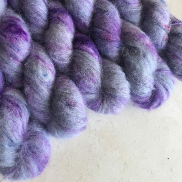 5 skiens of fluffy lavender yarn with neon purple speckles, placed at a diagonal angle from the top left corner of an off white, plastered background