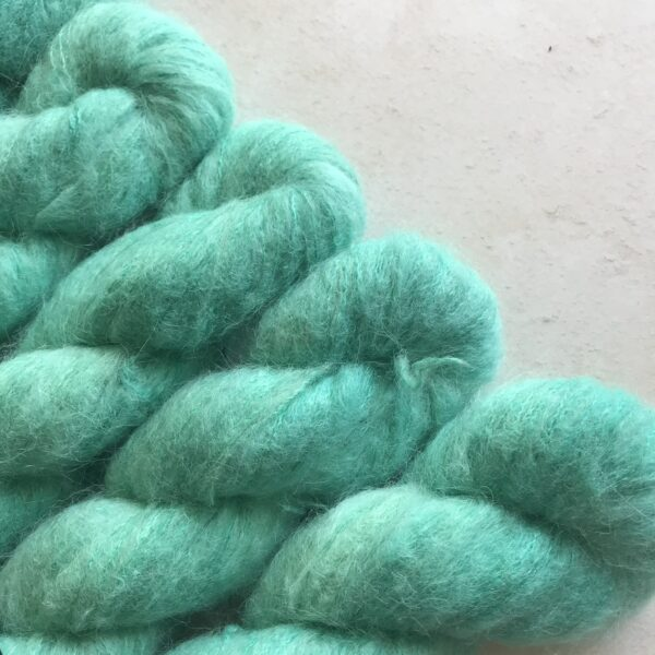 5 twisted skeins of soft, jade green fluffy yarn placed at a diagonal angle from the bottom left corner, on an off white plaster background