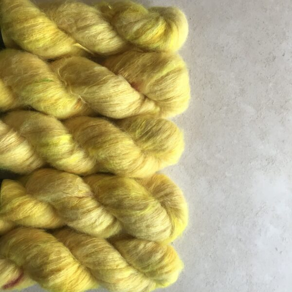 5 twisted skeins of daffodil yellow fluffy yarn with subtle yellow speckles. they are on an off white plaster, textured background and are lined up horizontally from the left hand side