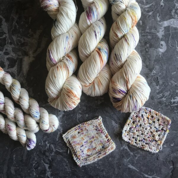 on a grey marble background are three skeins of natural yarn, gently speckled with blue, pink, orange, purple and yellow. they are placed at the top coming down towards the centre, with three mini skeins to the left. Knit and crochet swatches are placed towards the bottom of the image.
