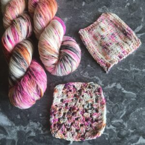 on a grey marble background are two twisted skeins, placed towards the left side of the image. They are heavily speckled with pinks, blacks and oranges with lots of white flashes. A crochet swatch is at the bottom centre, with a knit swatch towards the top right