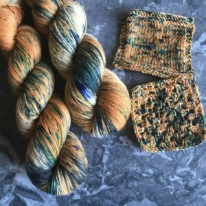 on a grey marble background are two twisted skeins, placed towards the left side of the image. The yarn is a soft orange with lots of black and blue speckles and white flashes. Knit and crochet swatches are shown towards the middle and top right