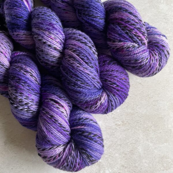 on an off white background are 3 tonal purple yarns on a diagonal angle from the top left. The yarn has one strand twisted throughout which moves from silver grey into black and back again.