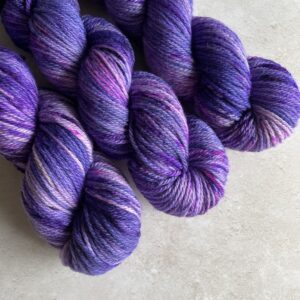 on an off white marble background are three skeins of tonal purple yarn, speckled with neon purple. They are placed at a diagonal from the top left corner.
