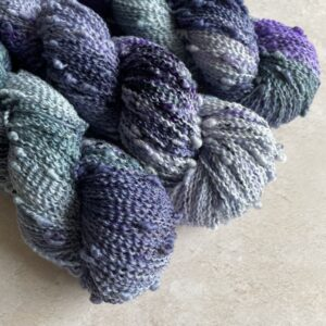on an off white background are three skeins of yarns at a diagonal from the top left. The yarn is dyed in semi-regular repeats of dark blue, purple and dark teal with some overlap and some lighter and darker areas. The yarn is slightly crimped with regular bobbles. It looks really fun and tactile