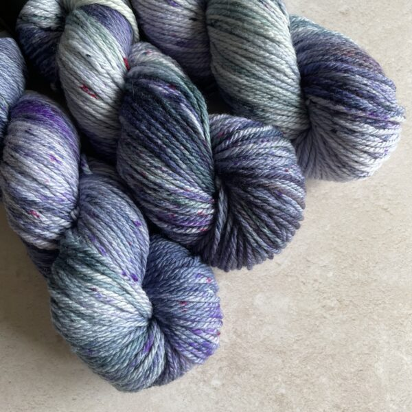 on an off white background are three twisted skeins of of yarn placed at a diagonal from the top left corner. They are dyed in shades of dark blue/grey, purple and teal, with lighter areas, blending and speckles in the same colours also.